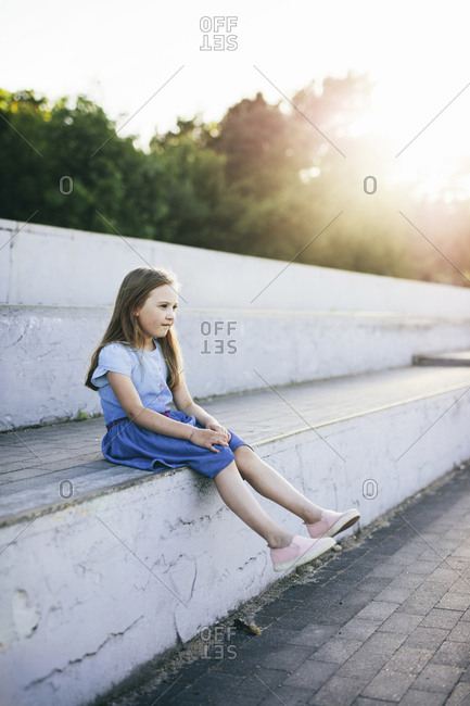 Thoughtful girl looking away while sitting on retaining wall against sky during sunset
