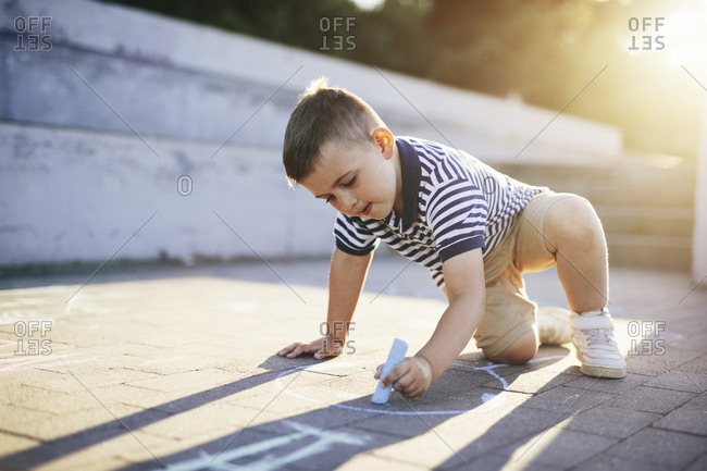 Boy drawing with chalk on footpath during sunset