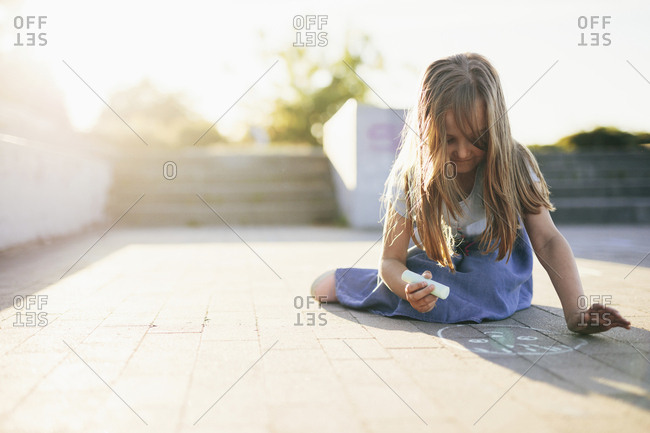 Girl drawing with chalk on footpath against sky during sunset