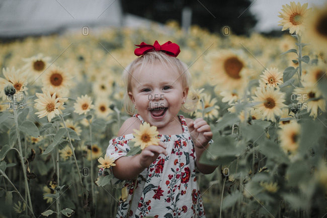 Portrait of cheerful baby girl standing amidst sunflower field