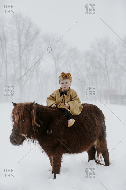 Portrait of cute girl sitting on pony amidst snow during foggy weather