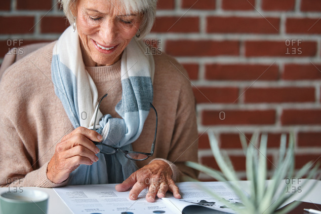 Senior woman planning retirement reading documents for life insurance financial investment