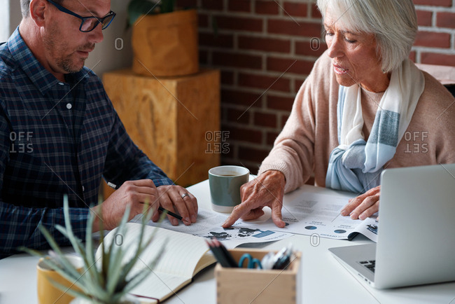 Old retired woman meeting with financial advisor discussing retirement savings plan