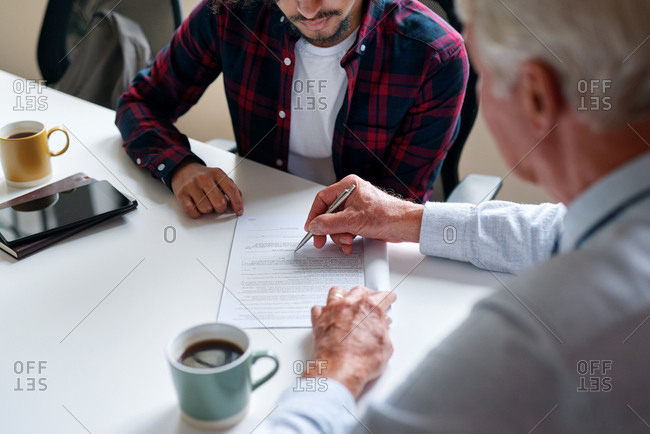 Financial Advisor Showing Student Where To Write Signature Holding Pen Young Man Applying For Loan