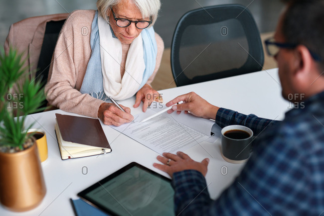 Old retired woman signing contract for life insurance with financial advisor showing where to write signature