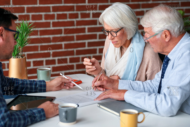 Senior couple planning retirement signing contract for life insurance savings plan with financial advisor showing where to write signature