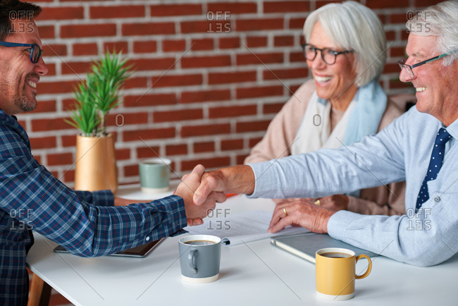 Senior couple shaking hands with financial advisor for successful retirement advice