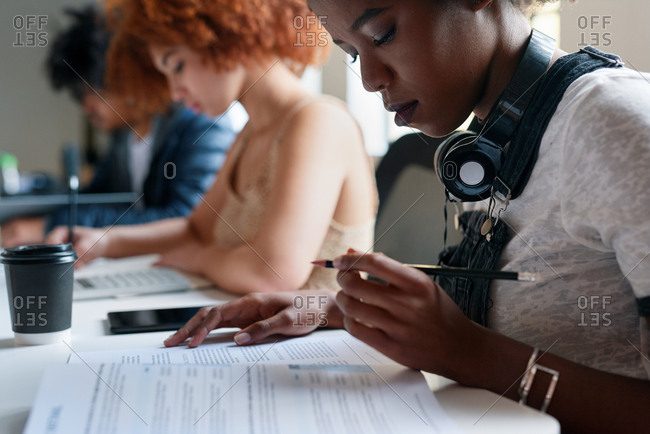 African american woman student writing exam test in class reading document holding pencil