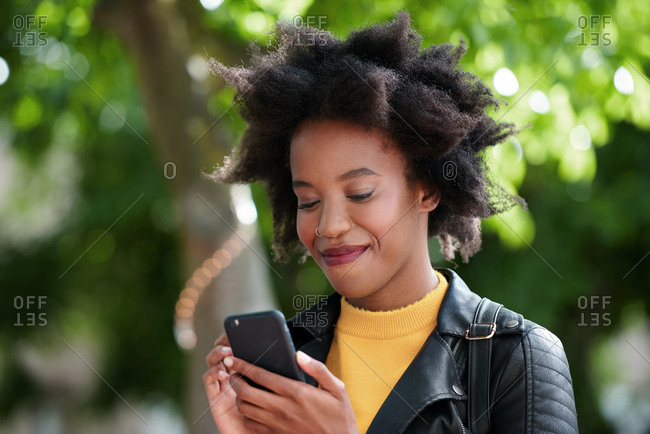 Young african american woman using smartphone texting outdoors browsing online messages stylish black female on mobile phone