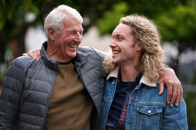 Father and son embracing laughing outdoors dad feeling proud showing affection happy family