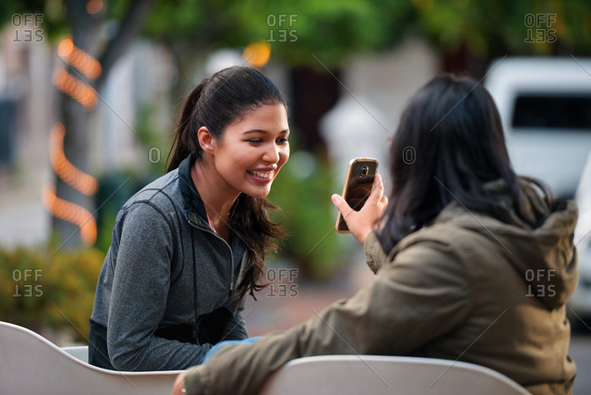Woman showing smartphone to best friend smiling happy looking at mobile phone best friends sitting on bench in city