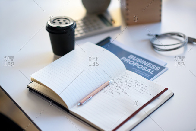 Notebook journal on desk list of goals in diary organized planner with notes