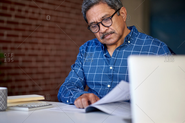 Mature man reading business documents at home wearing glasses