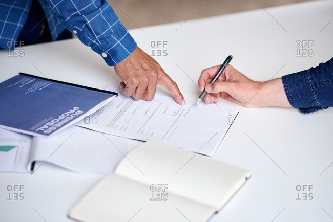 Business people hands signing contract document for corporate partnership deal