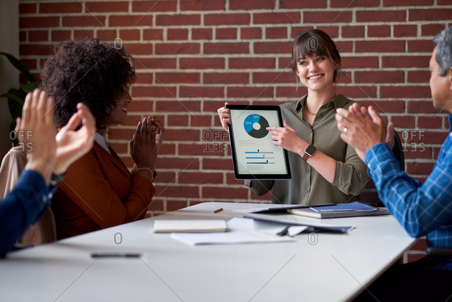 Happy business woman using digital tablet computer presenting financial data on screen with colleagues clapping hands congratulating successful solution