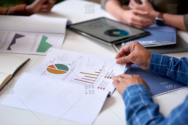 Businessman hands holding financial document discussing data with colleagues in meeting brainstorming ideas using graph statistics