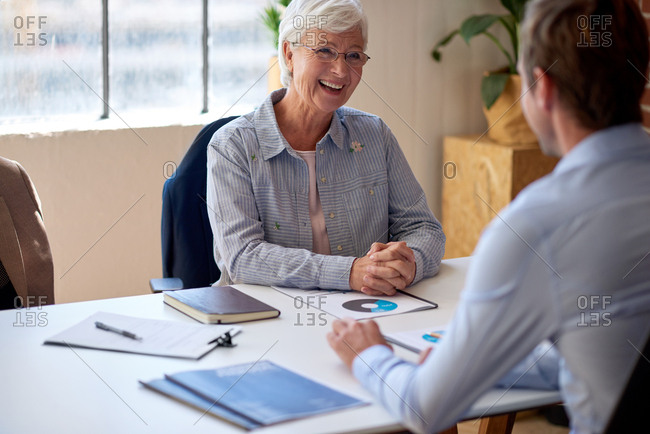 Happy old woman meeting with financial consultant discussing retirement plan
