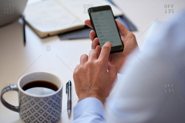 Businessman hands using smartphone browsing contacts reading information on mobile phone screen