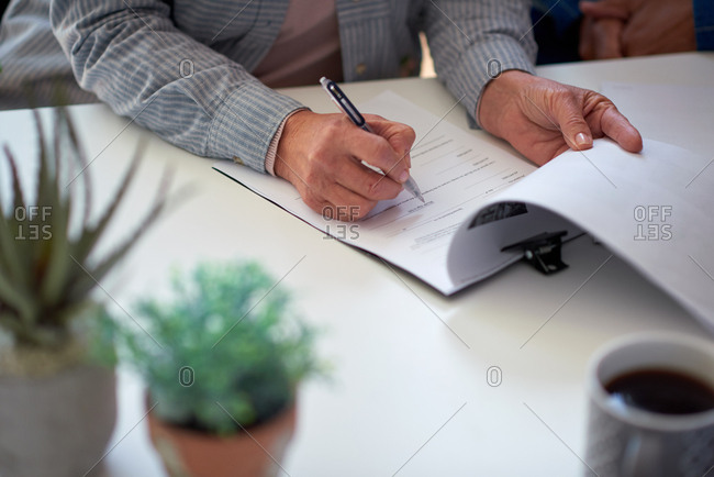 Businessman hands signing contract document for corporate partnership deal holding pen
