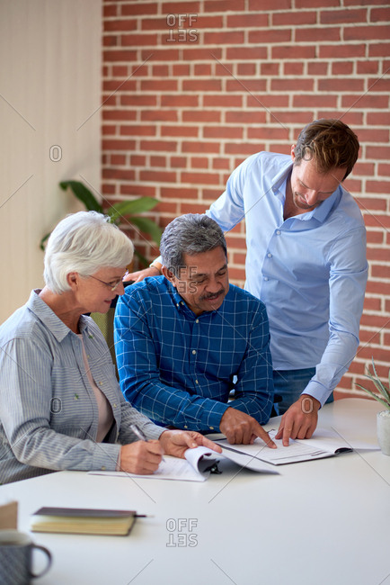 Senior couple signing contract planning retirement for life insurance savings plan with financial advisor showing where to write signature