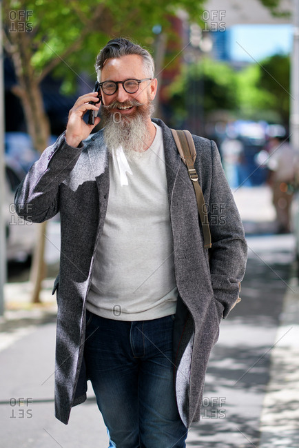 Stylish businessman using smartphone having phone call walking in city street