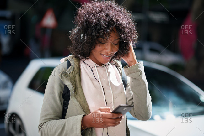 Young african american woman using smartphone browsing social media messages listening to music wearing headphones in city street
