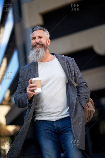Confident mature businessman man walking in city street holding coffee enjoying urban lifestyle