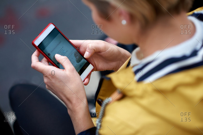 Young woman using smartphone texting sending messages on social media browsing online enjoying mobile technology in city