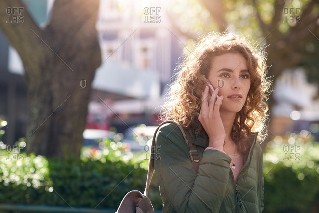 Beautiful woman using smartphone having phone call talking on mobile phone in city street with morning sun flare