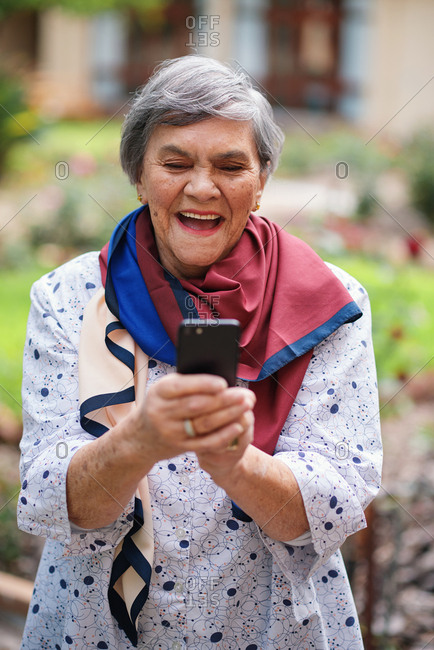 Happy senior woman using smartphone texting browsing messages on mobile phone in beautiful garden