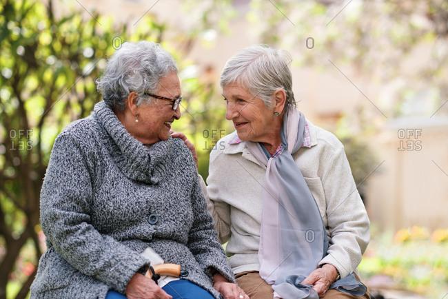 Two elderly women sitting on bench in park smiling happy life long friends enjoying retirement