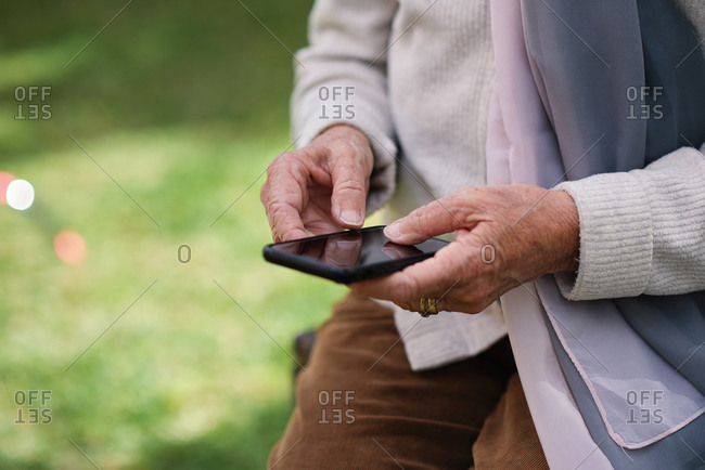 Old woman hands using smartphone texting sending messages on mobile phone outdoors