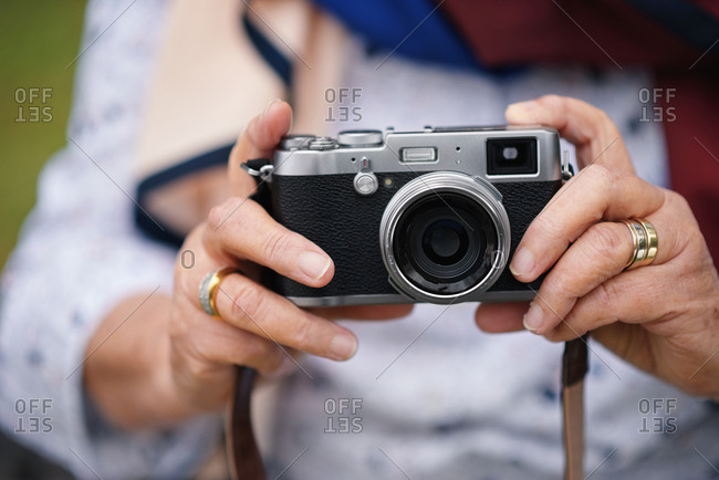 Old woman hands holding camera taking photo