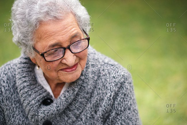 Portrait elderly woman sitting on bench in park smiling looking thoughtful enjoying retirement contemplating life