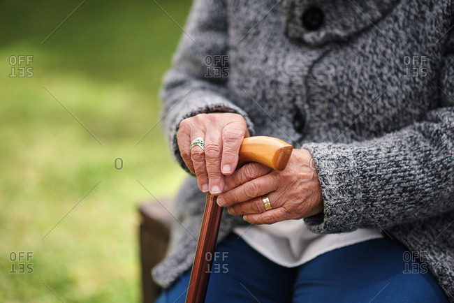 Old woman hands holding walking stick sitting on bench in park retirement lifestyle concept