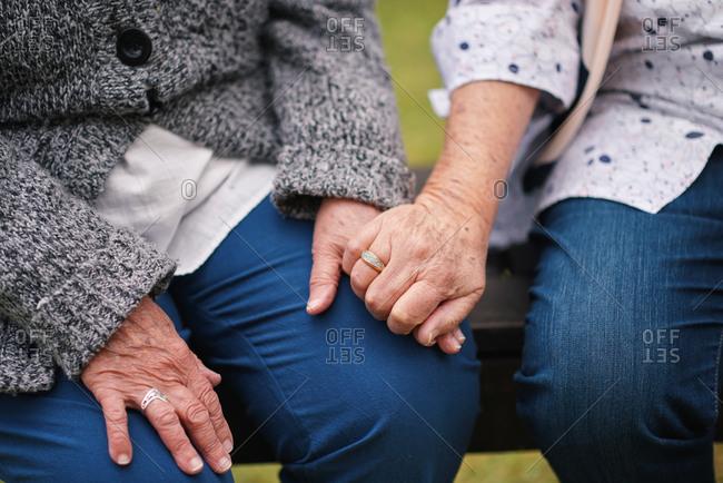 Two elderly women sitting on bench in park holding hands happy life long friends enjoying retirement