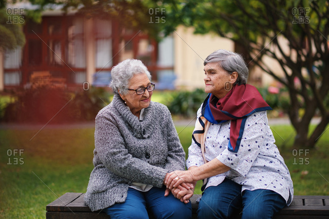 Two old women sitting on bench in park holding hands smiling happy life long friends enjoying retirement