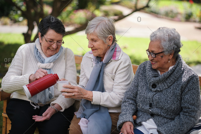 Happy old women sitting on bench in park drinking tea enjoying retirement together