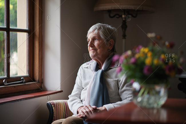 Happy elderly woman looking out window thinking of memories pensioner retirement lifestyle concept