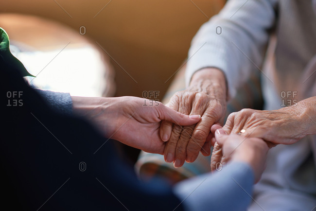 Nurse helping old woman holding hands in retirement home