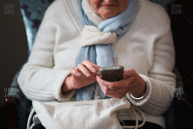 Happy elderly woman using smartphone texting browsing on mobile phone sending messages sitting on couch at home