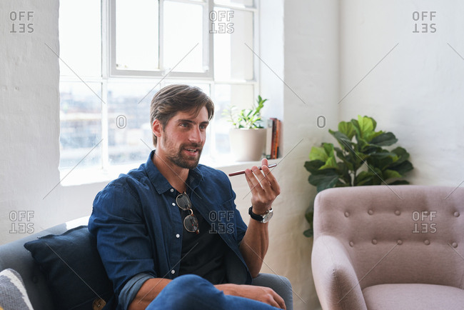 Attractive man using smartphone having phone call sitting on sofa at home
