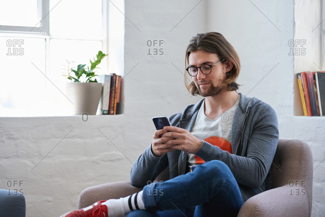 Young man using smartphone at home texting  reading social media messages browsing online