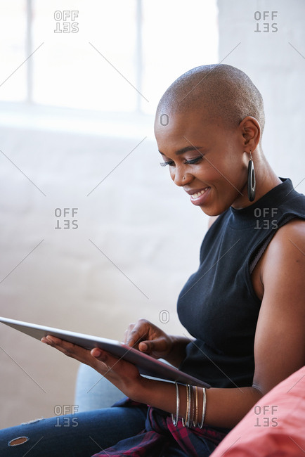 Bald african american woman using digital tablet computer at home