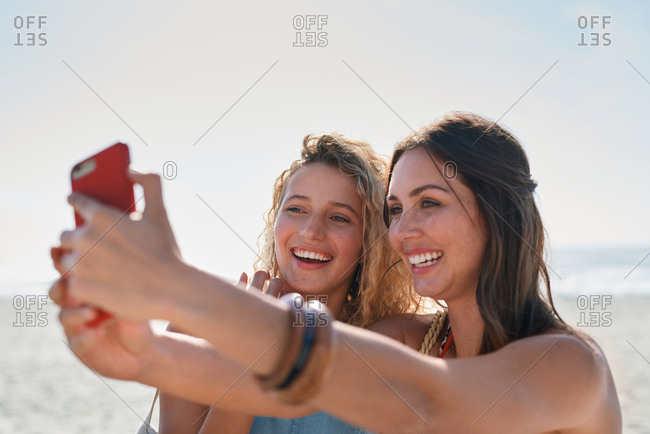 Beautiful woman friends taking photo using smartphone camera on beach smiling happy sharing vacation on social media