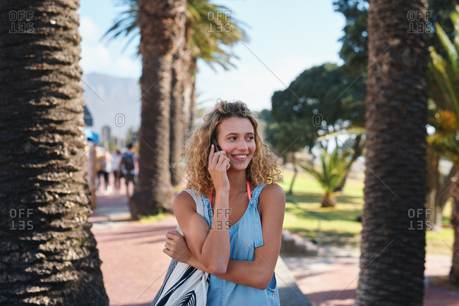 Beautiful tourist woman using smartphone on beachfront having phone call chatting on mobile phone enjoying summer vacation