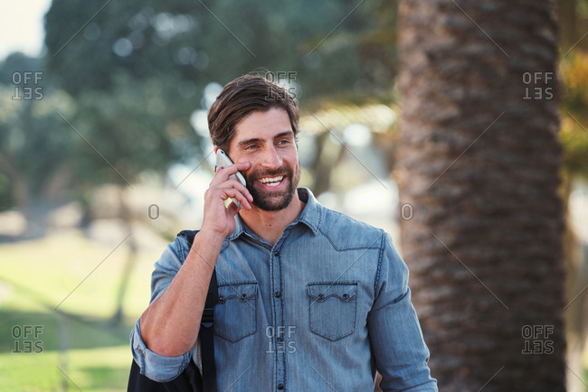 Attractive man using smartphone having phone call chatting on mobile phone outdoors