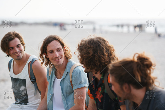 Group of male friends on beach enjoying summer holiday students having fun on vacation attractive guys hanging out on beachfront at sunset