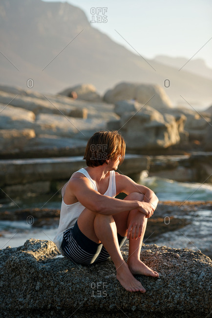Young man sitting on beach looking at sunset watching ocean contemplating journey
