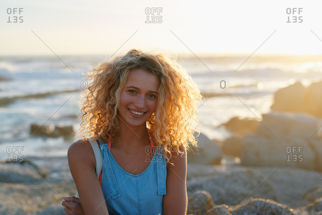 Portrait attractive blonde woman on beach at sunset smiling enjoying summer travel lifestyle on vacation